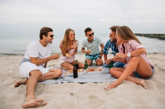 grupo-jovenes-sonrientes-chicos-chicas-descansando-juntos-playa-sentado-cerca-mar_8353-6895.jpg
